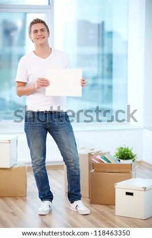 A young guy showing blank paper in new flat surrounded with boxes - stock photo