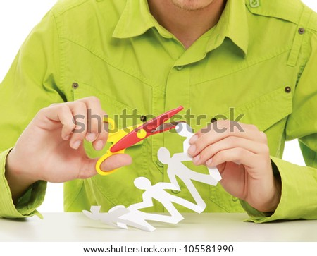 A young guy sitting at the desk, making paper people - stock photo