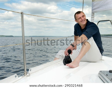 a young guy sitting on the deck of a yacht under sail and smiling  - stock photo
