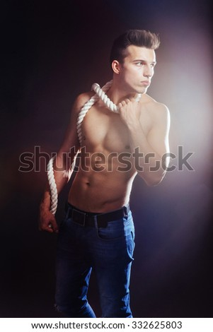 A young guy with a naked torso and rope.