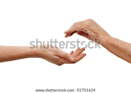 a young  hand holding an older one - stock photo