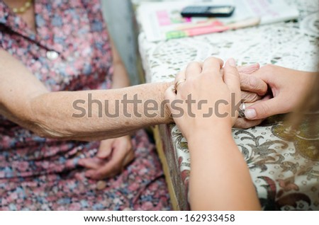 A young hand holding an senior pair of hands - stock photo