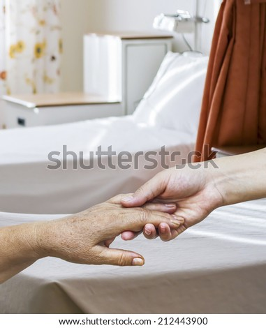 A young hand holds an old wrinkled hand in an hospital room. - stock photo