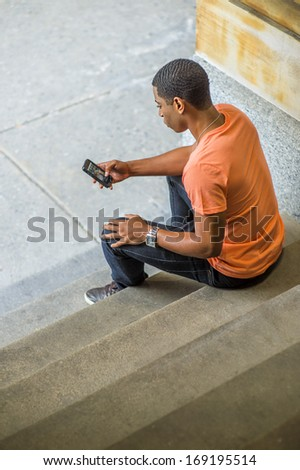 A young handsome black guy is sitting on stairs on the corner, checking messages on his mobile phone. /Text Anywhere - stock photo