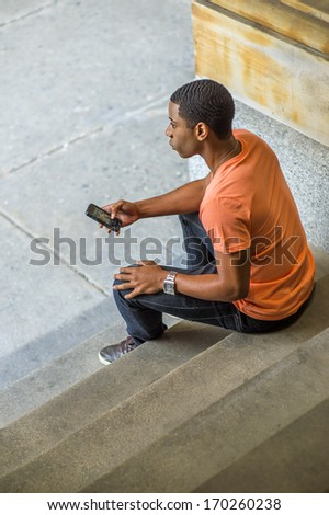 A young handsome black student is sitting on stairs on the corner, checking messages on his mobile phone and thinking / Text Anywhere - stock photo