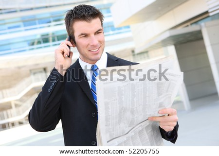 A young, handsome business man at the office building on phone with newspaper - stock photo