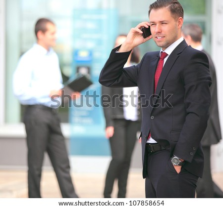 A young handsome business man on phone at office building - stock photo