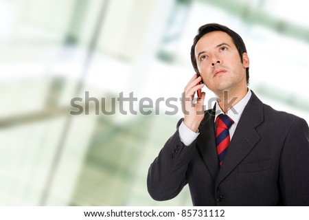 A young, handsome business man talking on the phone at a business environment