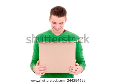 A young handsome caucasian man holding an open cardboard box in his hands and looking inside it - stock photo