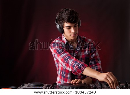 A young handsome deejay boy playing some music