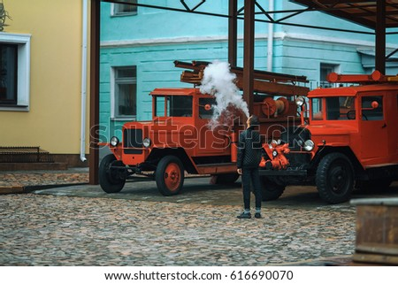 A young handsome guy is standing near old fire truck and is letting off steam from an electronic cigarette. Lifestyle.
