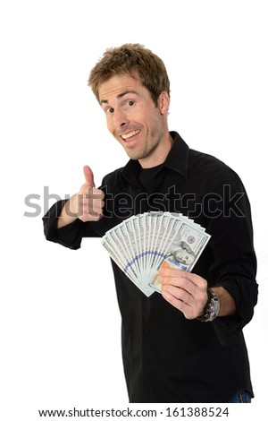 A young handsome man holding a lot of new hundred dollar bills and giving a thumbs up isolated on white background.  This newly redesigned US currency was released for circulation in October of 2013.