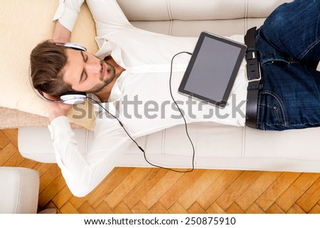 A young handsome man on the couch listening to music.  - stock photo