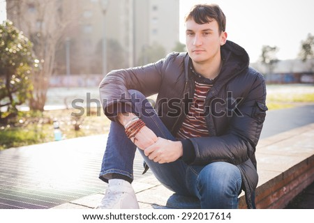 A young handsome man seated on a sidewalk, when in the city is getting dusk, wearing blue jeans and a blue jacket.