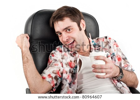 A young handsome white guy sitting on a Caucasian black chair in a colorful Hawaiian shirt with a clock in his hand and holding a glass of drink in isolation over white - stock photo