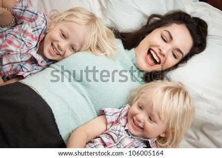 A young happy and beautiful mother lying down playing and laughing with her two cute children. - stock photo