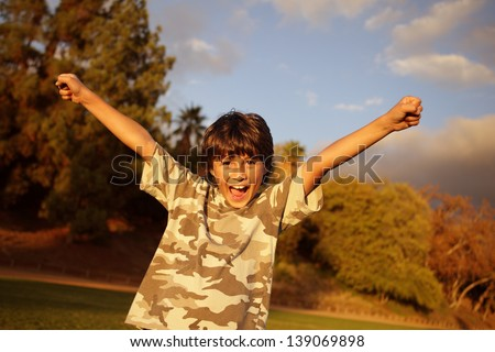 A young happy boy celebrates with arms outstretched in the golden light at sunset - stock photo