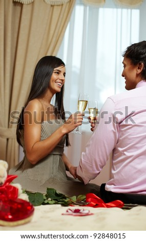 A young happy couple making toast with champagne