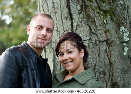 A young happy couple outdoor by a tree on a fall day. - stock photo