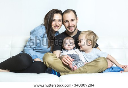 A Young happy family with two children at home - stock photo