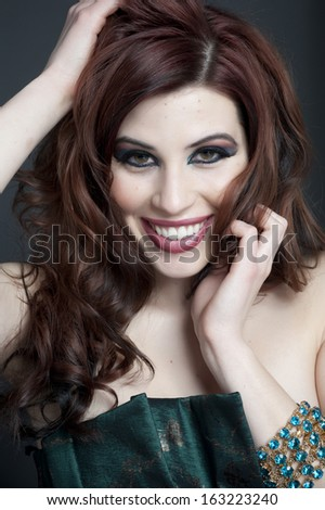 A young happy female model headshot in a studio. - stock photo