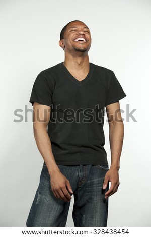 A young happy hip African American male wearing a black t-shirt in a studio setting on a white background. - stock photo