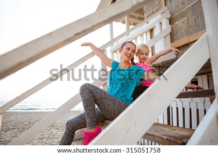 A young, happy mother shows her young daughter how to fly. They are playing and pretending to be seagulls, flying high up above the water. Both are wearing fitness gear. - stock photo