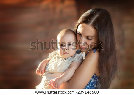 A young happy smiling mother with her little baby against wall of red brick.  - stock photo