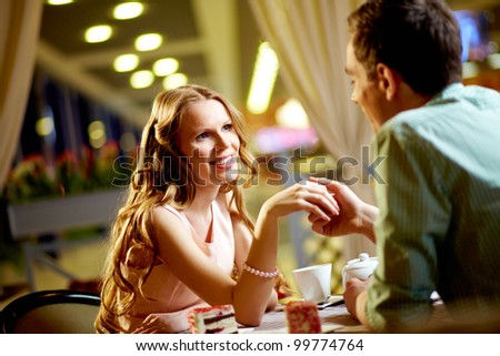 A young happy woman and her boyfriend sitting in restaurant - stock photo