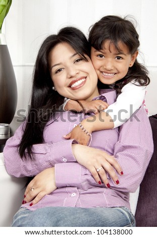 A young happy woman hugs an child girl happy - stock photo