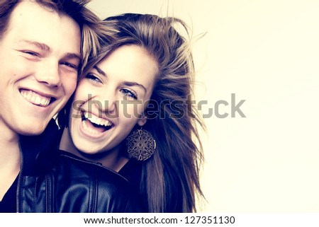 A young high school boy and his girlfriend being photographed. - stock photo