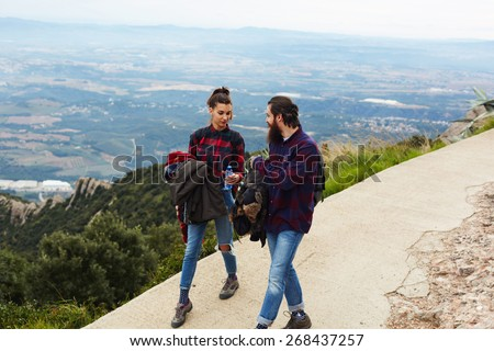 A young hiker woman giving the bottle of water to her friend, couple walking on the trail with beautiful horizon view from altitude
