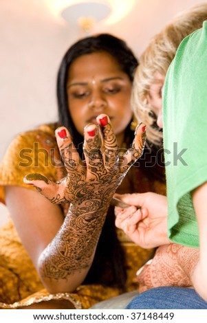 A young Hindu bride receives traditional Henna designs on her arms and hands - stock photo