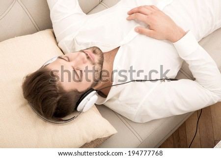 A young Hipster styled man listening music on the sofa with headphones.