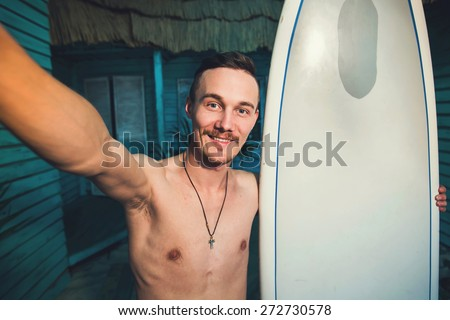 A young hipster surfer making selfie with his surf at beach house at ocean side - stock photo
