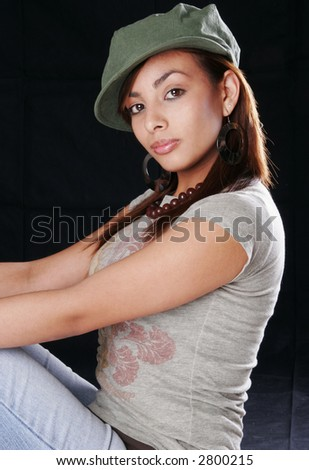 A young Hispanic girl posing in the studio with a cap and t-shirt