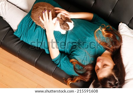 A young hispanic girl with a rabbit on the sofa.   - stock photo