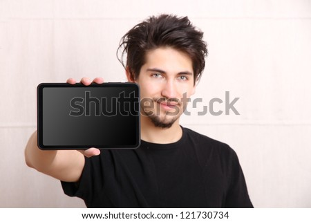 A young hispanic man holding a Tablet PC. - stock photo