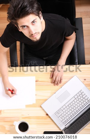 A young hispanic man working on a wooden desk with a laptop.