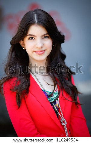 A young hispanic teen woman smiles at the camera in an outdoor setting. - stock photo