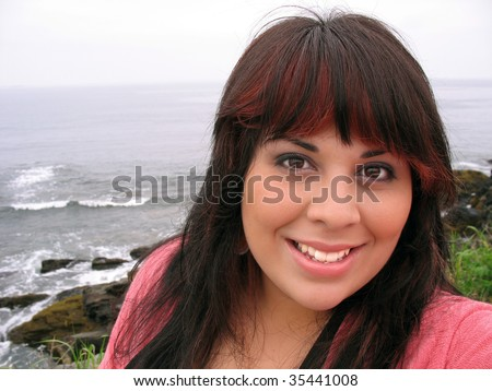 A young hispanic woman with red highlights in her hair by the sea shore in Newport Rhode Island.