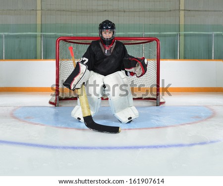 A Young Hockey Goalie Kid Protects his Net from a Goal - stock photo
