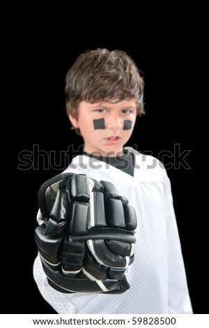 A young hockey player gives a fist with his protective glove.  Selective focus is on the glove. - stock photo