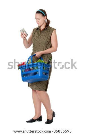 A young housewife in a supermarket scenario reading a label on a can.