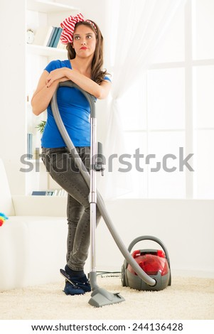 A young housewife standing leaning on vacuum cleaner tired of housework. - stock photo