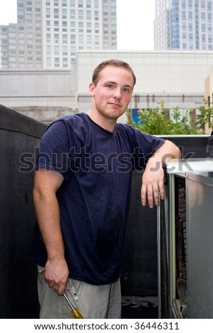 A young HVAC technician working on a rooftop. - stock photo