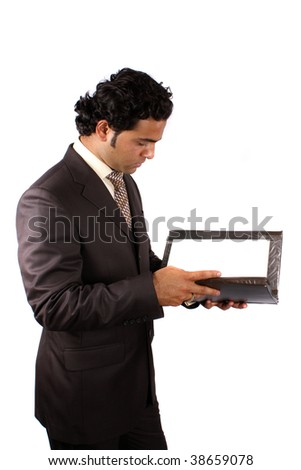 A young Indian businessman reading documents from a file, on white studio background.