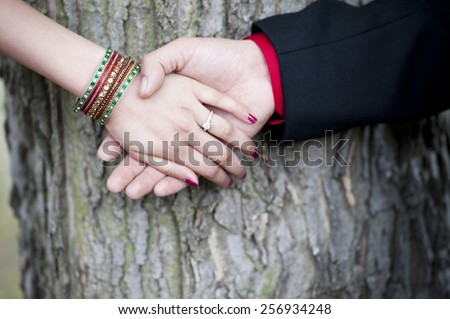 A young Indian couple's engagement hands on a sunny day outdoors. - stock photo
