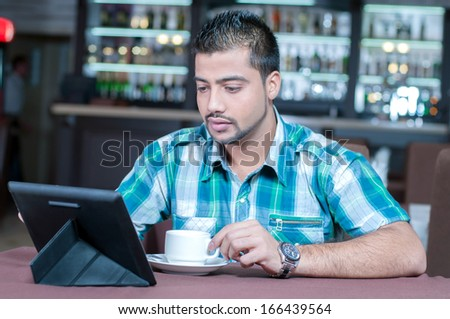 A young Indian guy in a cafe working on tablet - stock photo