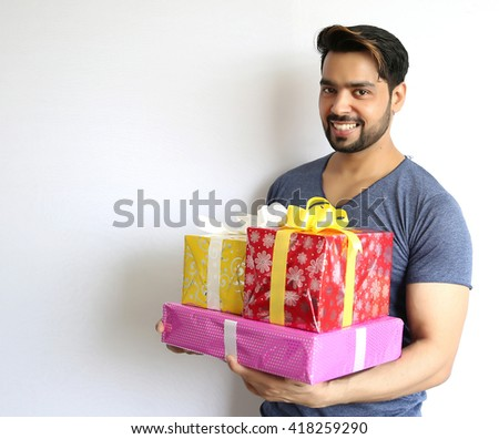 A young indian man holding gift box, christmas, valentine's day, birthday, happiness concept  - stock photo